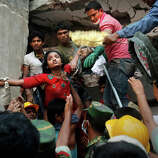 A Bangladeshi woman survivor is lifted out of the rubble by rescuers at the site of a building that collapsed Wednesday in Savar, near Dhaka, Bangladesh, Thursday, April 25, 2013. The collapse of Rana Plaza in Dhaka that killed 1,129 people.