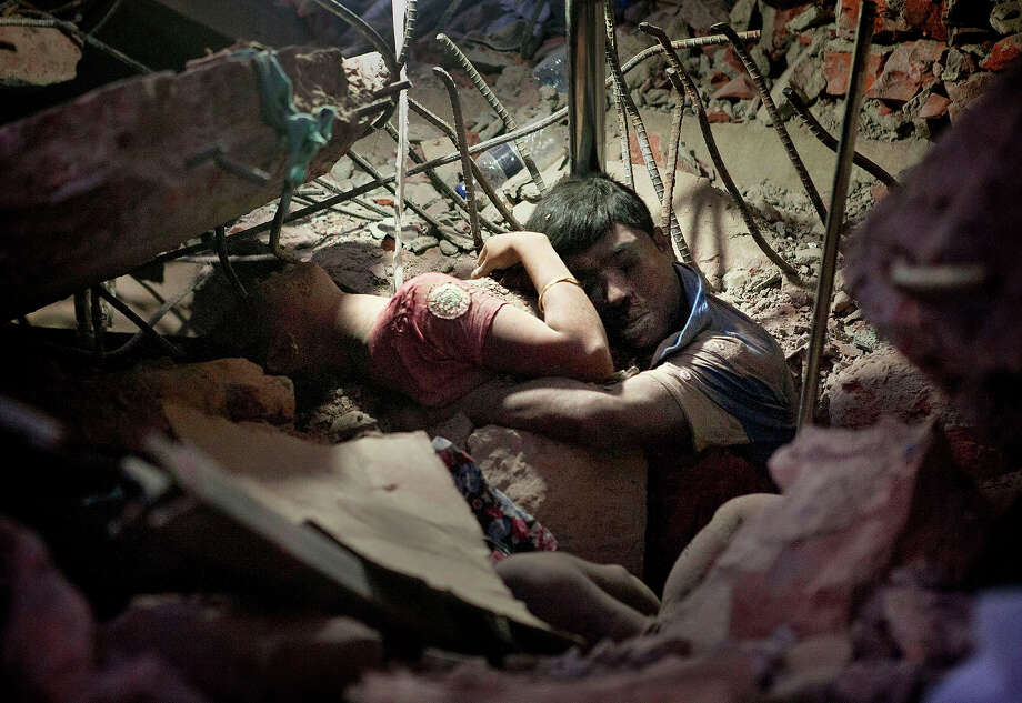 A Bangladeshi man holds on to a woman, both victims of a building collapse, in the debris of Rana Plaza garment factory in Savar near Dhaka, Bangladesh, April 25, 2013. The collapse of Rana Plaza in Dhaka that killed 1,129 people. Photo: Suman Paul, ASSOCIATED PRESS / AP2013