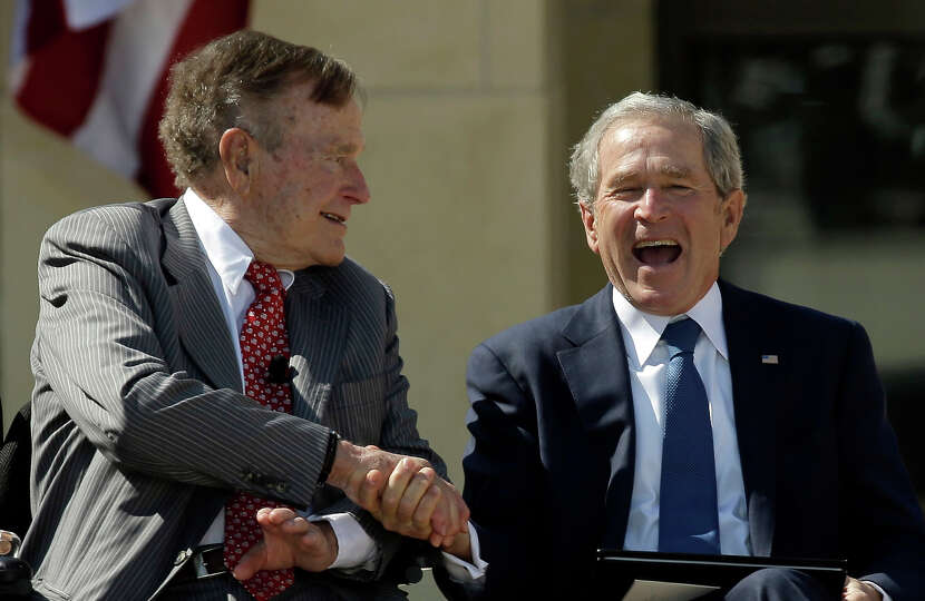 Former President George H.W. Bush shakes hands with his son, former President George W. Bush during