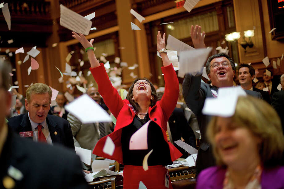 Georgia Rep. Mandi Ballinger, R-Canton, center, Rep. Terry Rogers, RñClarkesville, left, and Rep. Rick Jasperse, R-Jasper, right, throw up paper from their desks at the conclusion of the legislative session in the House chamber, Thursday, March 28, 2013, in Atlanta. Photo: David Goldman, ASSOCIATED PRESS / AP2013