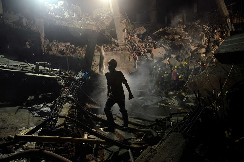 A worker leaves the site where a garment factory building collapsed near Dhaka, Bangladesh Monday, A
