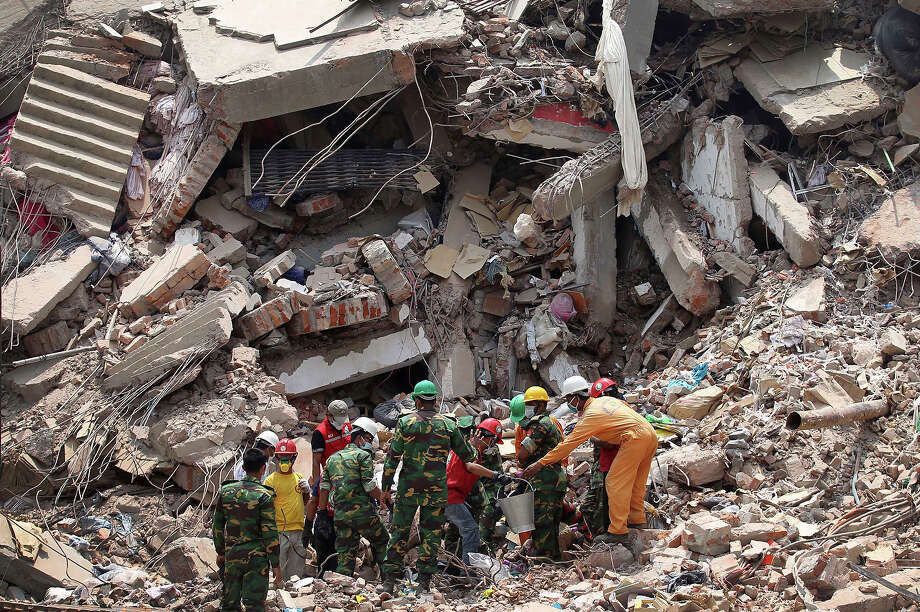 Workers try to release two bodies trapped in the rubble of collapsed Rana Plaza garment factory building in Savar, near Dhaka, Bangladesh, April 30, 2013. The collapse of Rana Plaza in Dhaka that killed 1,129 people. Photo: Wong Maye-E, ASSOCIATED PRESS / AP2013