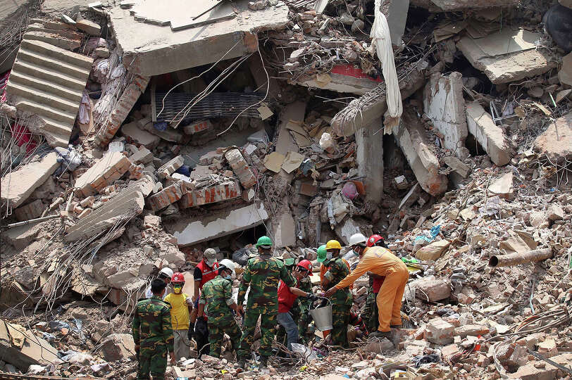 Workers try to release two bodies trapped in the rubble of collapsed Rana Plaza garment factory buil
