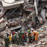 Workers try to release two bodies trapped in the rubble of collapsed Rana Plaza garment factory building in Savar, near Dhaka, Bangladesh, April 30, 2013. The collapse of Rana Plaza in Dhaka that killed 1,129 people.