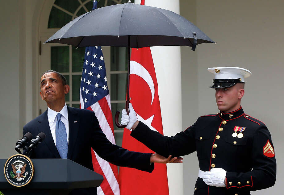 President Barack Obama looks to see if it is still raining as a Marine holds an umbrella for him during his joint news conference with Turkish Prime Minister Recep Tayyip Erdogan, not pictured, Thursday, May 16, 2013, in the Rose Garden of the White House in Washington. Photo: Charles Dharapak, ASSOCIATED PRESS / AP2013