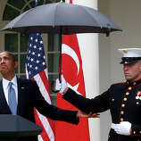 President Barack Obama looks to see if it is still raining as a Marine holds an umbrella for him during his joint news conference with Turkish Prime Minister Recep Tayyip Erdogan, not pictured, Thursday, May 16, 2013, in the Rose Garden of the White House in Washington.