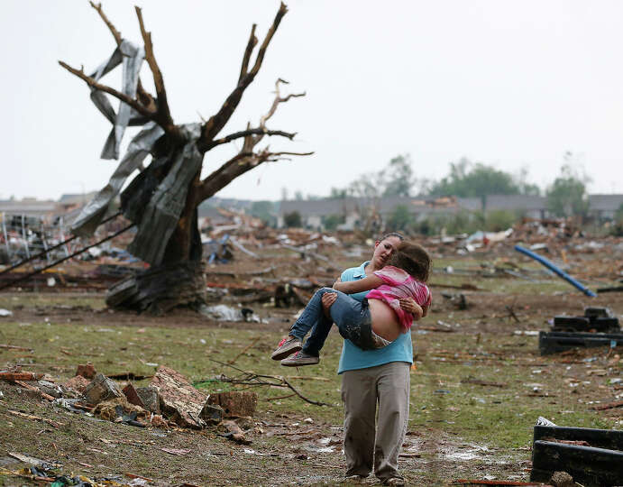 A woman carries her child through a field near the collapsed Plaza Towers Elementary School in Moore