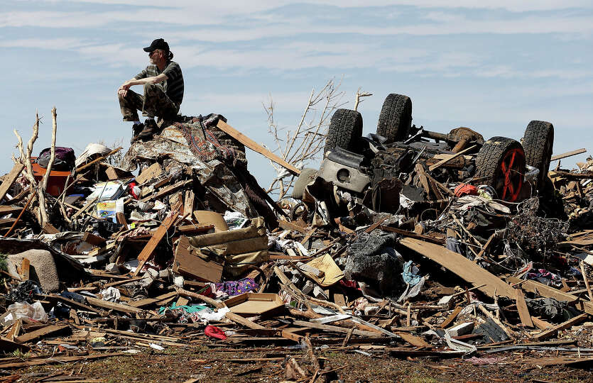 David Lee Estep sits atop a pile of rubble that was the home he shared with his parents Thursday, Ma