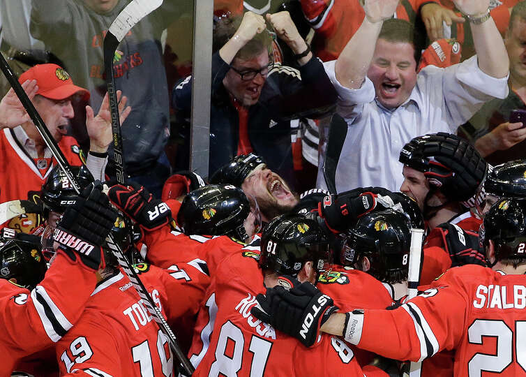 Chicago Blackhawks defenseman Brent Seabrook, center, looking up, celebrates with his teammates afte