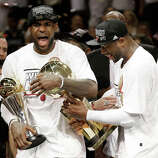 The Miami Heat's Dwyane Wade, right, holds the Larry O'Brien NBA Championship Trophy as  LeBron James holds his Bill Russell NBA Finals Most Valuable Player Award after Game 7 of the NBA basketball championship game against the San Antonio Spurs, Friday, June 21, 2013, in Miami. The Miami Heat defeated the San Antonio Spurs 95-88 to win their second straight NBA championship.