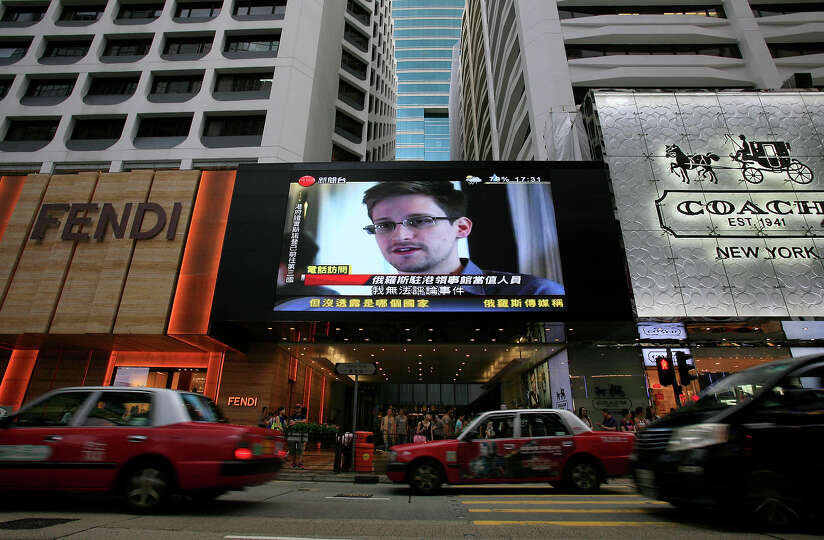 A TV screen shows a news report of Edward Snowden, a former CIA employee who leaked top-secret docum