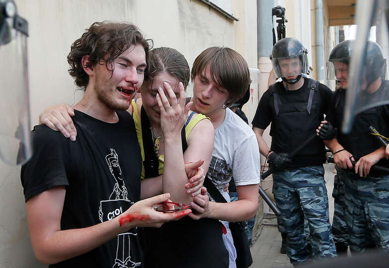 Riot police (OMON) guard gay rights activists who have been beaten by anti-gay protesters during an