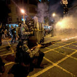 Military police fire tear gas at protestors near Maracana stadium where Brazil and Spain are playing the final Confederations Cup soccer match in Rio de Janeiro, Brazil, Sunday, June 30, 2013. Anti-government protesters are marched near the Maracana football stadium during the major international match, venting their anger about the billions of dollars the Brazilian government is spending on major sporting events rather than public services.