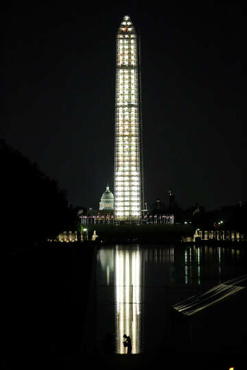 The Washington Monument is lit while undergoing repairs, with the U.S. Capitol behind, Monday, July