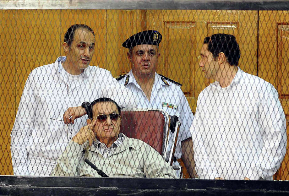 Former Egyptian President Hosni Mubarak, seated, and his two sons Gamal Mubarak, left, and Alaa Mubarak, right, attend a hearing in a courtroom at the Police Academy, Cairo, Egypt, Saturday, Sept. 14, 2013. Egypt's ousted long-time autocrat was back in court, grinning and waving for the resumption of his retrial on charges related to the killings of some 900 protesters during the 2011 uprising that led to his ouster. Photo: Ahmed Omar, ASSOCIATED PRESS / AP2013