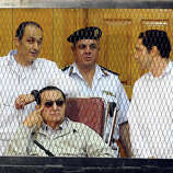 Former Egyptian President Hosni Mubarak, seated, and his two sons Gamal Mubarak, left, and Alaa Mubarak, right, attend a hearing in a courtroom at the Police Academy, Cairo, Egypt, Saturday, Sept. 14, 2013. Egypt's ousted long-time autocrat was back in court, grinning and waving for the resumption of his retrial on charges related to the killings of some 900 protesters during the 2011 uprising that led to his ouster.