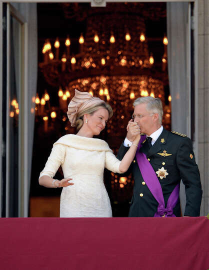 Belgium's King Philippe, right, kisses the hand of Queen Mathilde as they stand on the balcony of th