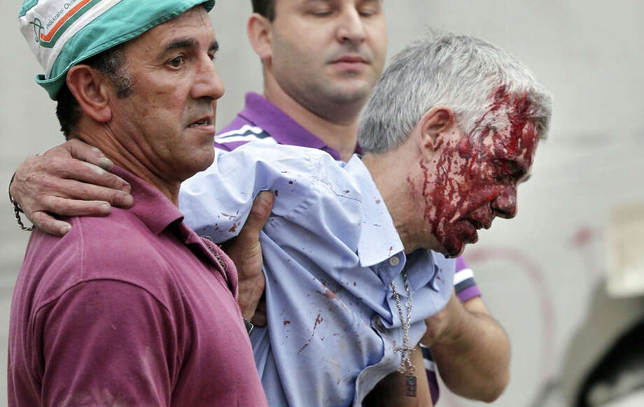 In this photo taken on Wednesday July 24 2013, train driver Francisco Jose Garzon Amo is helped by two men as he is evacuated from the site of a train accident in Santiago de Compostela, Spain. Photo: La Voz De Galicia/Xoan Soler, ASSOCIATED PRESS / AP2013