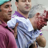 In this photo taken on Wednesday July 24 2013, train driver Francisco Jose Garzon Amo is helped by two men as he is evacuated from the site of a train accident in Santiago de Compostela, Spain.