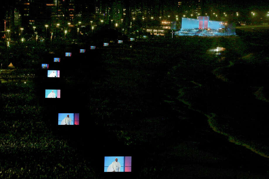 Pope Francis is projected on video screens lining the Copacabana beachfront in Rio de Janeiro, Brazil, Friday, July 26, 2013. Francis presided over one of the most solemn rites of the Catholic Church, a procession re-enacting Christ's crucifixion, that received a Broadway-like treatment; staging a wildly theatrical telling of the Stations of the Cross, complete with huge stage sets, complex lighting, a full orchestra and a cast of hundreds acting out a modern version of the biblical story. Photo: Jorge Saenz, ASSOCIATED PRESS / AP2013