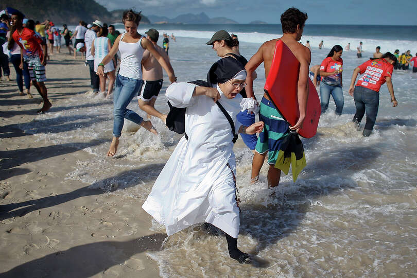 A nun reacts as the tide comes in fast on Copacabana beach in Rio de Janeiro, Brazil, Saturday, July