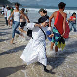 A nun reacts as the tide comes in fast on Copacabana beach in Rio de Janeiro, Brazil, Saturday, July 27, 2013. Pope Francis was to preside over an evening vigil service on Copacabana beach that was expected to draw more than 1 million young people.
