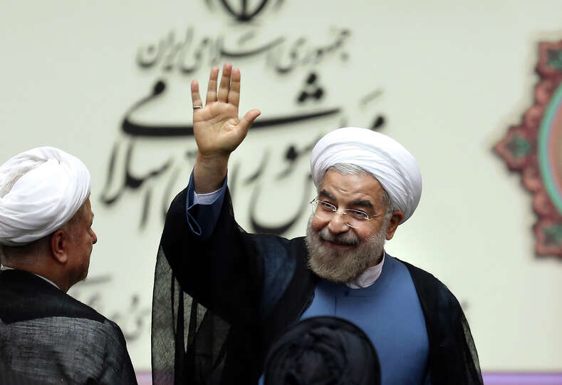 Iran's new President Hasan Rouhani, waves after swearing in at the parliament, in Tehran, Iran, Sund