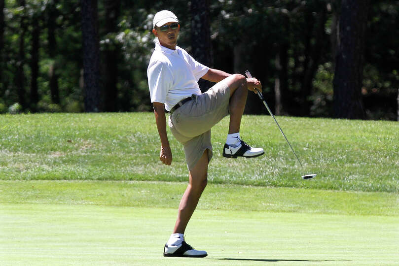 President Barack Obama reacts as he misses a shot while golfing on the first hole at Farm Neck Golf