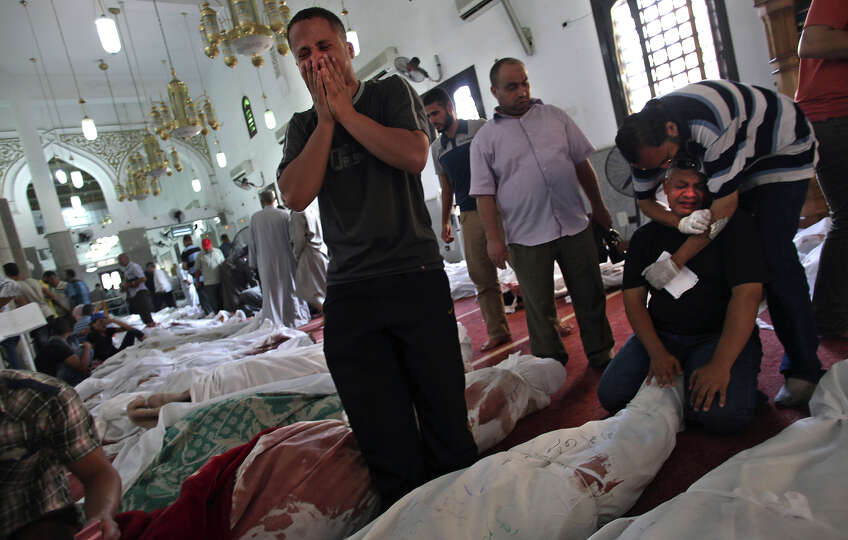 Egyptians mourn over the bodies of their relatives in the El-Iman mosque at Nasr City, Cairo, Egypt,