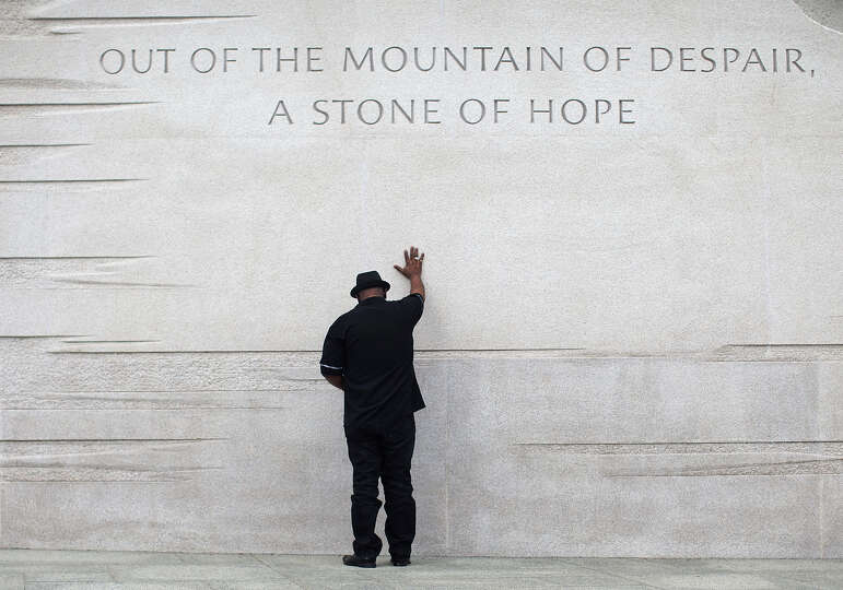 Rev. Bobby Turner or Columbus, Ohio, places his hand on the Martin Luther King Jr. Memorial, Thursda