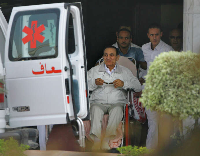 Former Egyptian President Hosni Mubarak, 85, is escorted by medical and security personnel into an a