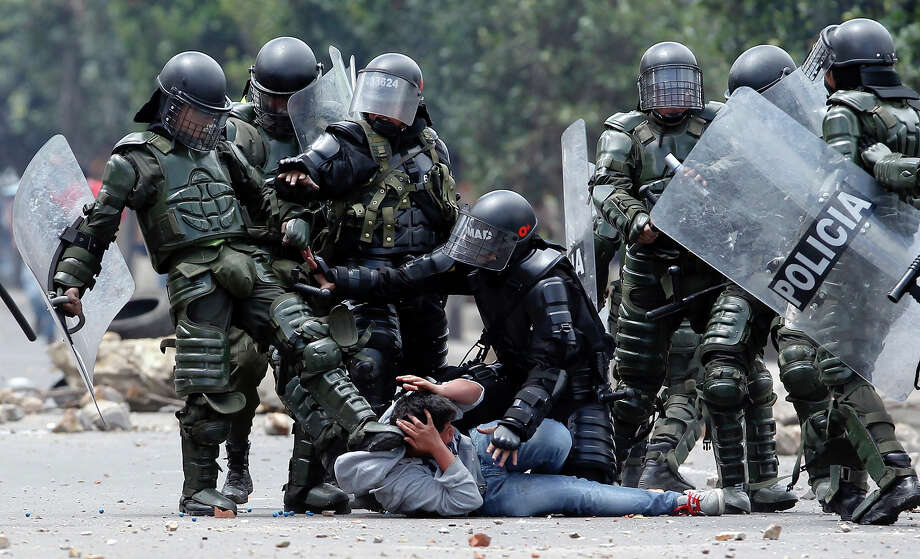 A riot police officer, left, kicks a protester as another, center, tries to protect him before his arrest during protests in Ubate, north of Bogota, Colombia, Monday, Aug. 26, 2013.  Hundreds of protesters clashed with police in support of farmers who have being blockading Colombian highways for a week for an assortment of demands that include reduced gasoline prices, increased subsidies and the cancellation of free trade agreements. Photo: Fernando Vergara, ASSOCIATED PRESS / AP2013