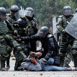 A riot police officer, left, kicks a protester as another, center, tries to protect him before his arrest during protests in Ubate, north of Bogota, Colombia, Monday, Aug. 26, 2013.  Hundreds of protesters clashed with police in support of farmers who have being blockading Colombian highways for a week for an assortment of demands that include reduced gasoline prices, increased subsidies and the cancellation of free trade agreements.