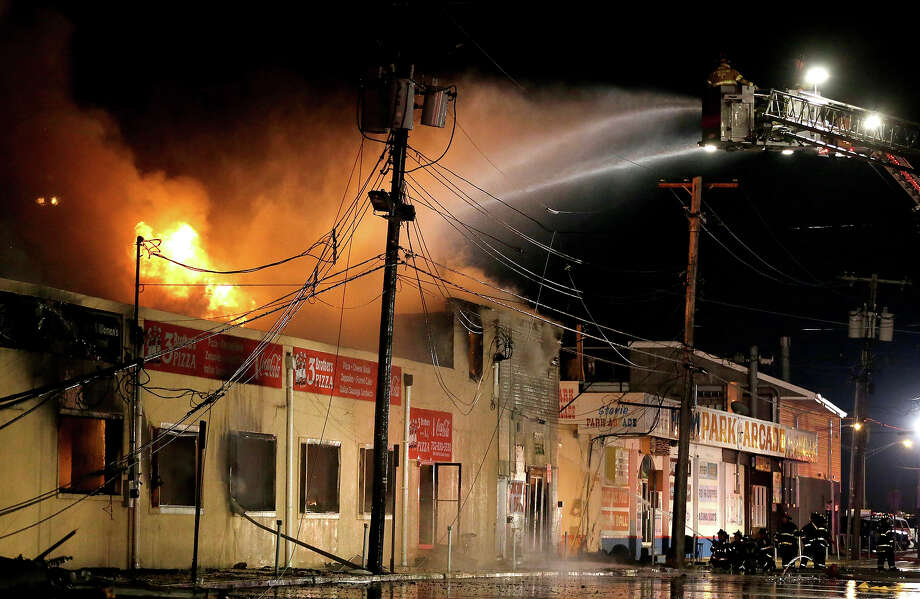 Firefighters battle a blaze in a building on the Seaside Park boardwalk on Thursday, Sept. 12, 2013, in Seaside Park, N.J. The fire began in a frozen custard stand on the Seaside Park section of the boardwalk and quickly spread north into neighboring Seaside Heights. Photo: Julio Cortez, ASSOCIATED PRESS / AP2013