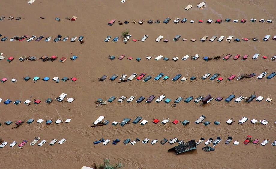 A field of parked cars and trucks sits partially submerged near Greeley, Colo., Saturday, Sept. 14, 2013, as debris-filled rivers flooded into towns and farms miles from the Rockies. Hundreds of roads, farms and businesses in the area were damaged or destroyed by the floodwaters. Photo: John Wark, ASSOCIATED PRESS / AP2013
