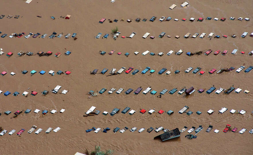 A field of parked cars and trucks sits partially submerged near Greeley, Colo., Saturday, Sept. 14,