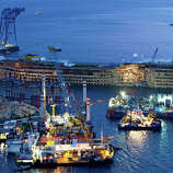 """The Costa Concordia is seen after it was lifted upright, on the Tuscan Island of Giglio, Italy, early Tuesday morning, Sept. 17, 2013. The crippled cruise ship was pulled completely upright after a complicated, 19-hour operation to wrench it from its side where it capsized last year off Tuscany, with officials declaring it a """"perfect"""" end to a daring and unprecedented engineering feat."""