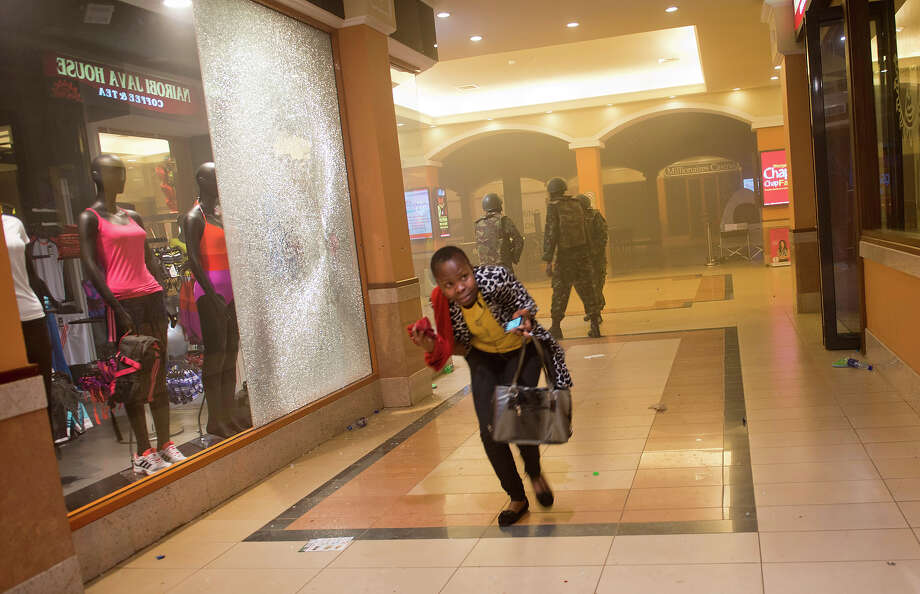 A woman who had been hiding during the gun battle runs for cover after armed police enter the Westgate Mall in Nairobi, Kenya, after gunmen threw grenades and opened fire Sept. 21, 2013. Photo: Jonathan Kalan, ASSOCIATED PRESS / AP2013