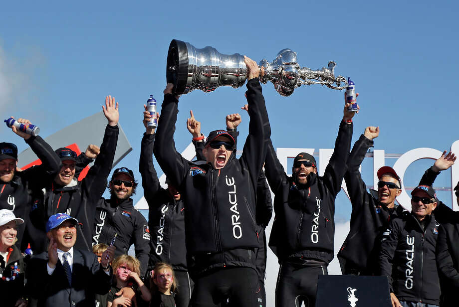 Oracle Team USA skipper Jimmy Spithill holds up the Auld Mug as they celebrate in the podium after winning the America's Cup sailing event over Emirates Team New Zealand on Wednesday, Sept. 25, 2013, in San Francisco. Photo: Marcio Jose Sanchez, ASSOCIATED PRESS / AP2013