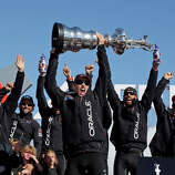 Oracle Team USA skipper Jimmy Spithill holds up the Auld Mug as they celebrate in the podium after winning the America's Cup sailing event over Emirates Team New Zealand on Wednesday, Sept. 25, 2013, in San Francisco.