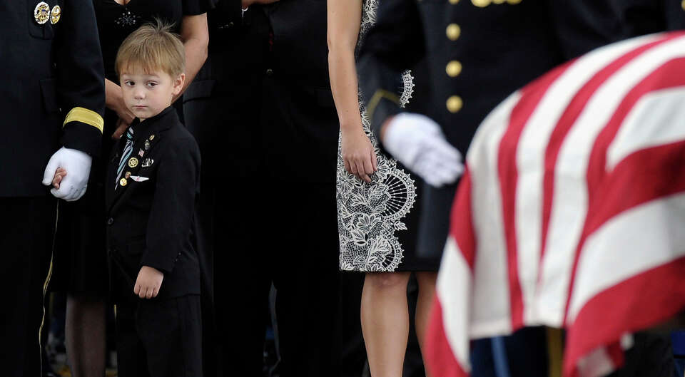 Kaden Bowden, son of U.S. Army Staff Sgt. Joshua J. Bowden, looks at the casket for his father durin