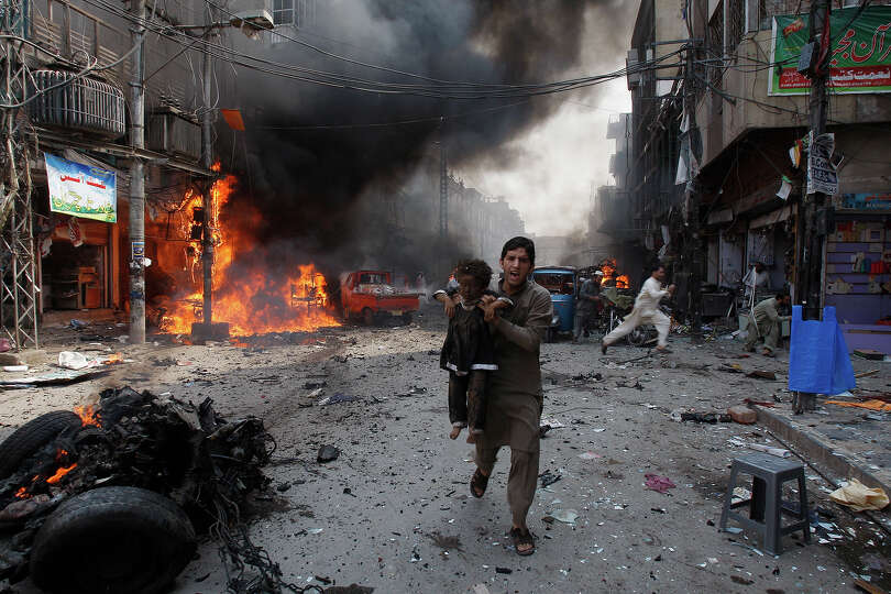 A Pakistani man carrying a child rushes away from the site of a blast shortly after a car exploded i