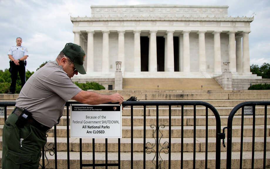 A US Park Police officer watches at left as a National Park Service employee posts a sign on a barricade closing access to the Lincoln Memorial in Washington, Tuesday, Oct. 1, 2013. Congress plunged the nation into a partial government shutdown as a long-running dispute over President Barack Obama's health care law stalled a temporary funding bill, forcing about 800, 000 federal workers off the job and suspending most non-essential federal programs and services. Photo: Carolyn Kaster, ASSOCIATED PRESS / AP2013