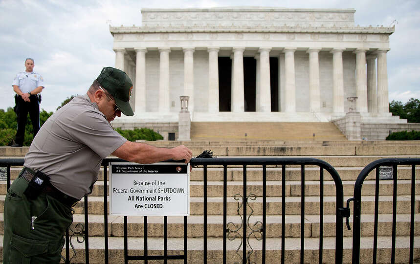 A US Park Police officer watches at left as a National Park Service employee posts a sign on a barri
