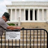 A US Park Police officer watches at left as a National Park Service employee posts a sign on a barricade closing access to the Lincoln Memorial in Washington, Tuesday, Oct. 1, 2013. Congress plunged the nation into a partial government shutdown as a long-running dispute over President Barack Obama's health care law stalled a temporary funding bill, forcing about 800, 000 federal workers off the job and suspending most non-essential federal programs and services.