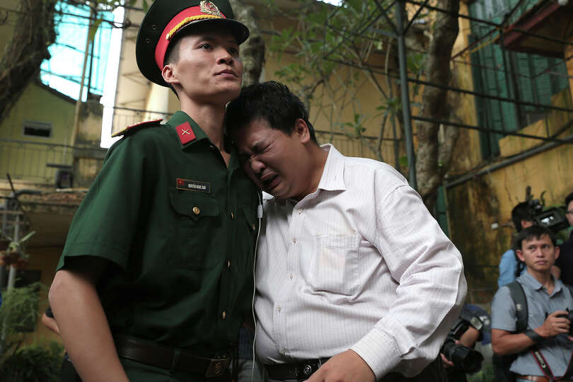 A man cries on a military officer in the garden of the house of the late Gen. Vo Nguyen Giap in Hano