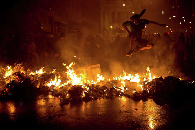 A demonstrator with his face covered jumps over a burning barricade at the Cinelandia square during