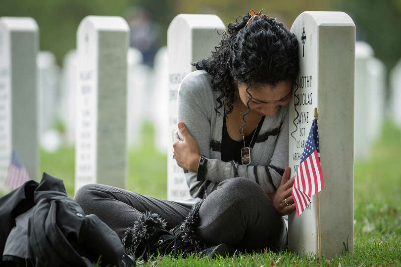 Thania Sayne of Effingham, Ill., leans on the headstone at the grave of her husband, Army Sgt. Timot