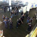 In this photo provided to the AP, which has been authenticated based on its contents and other AP reporting, police officers stand near an unidentified weapon in Terminal 3 of the Los Angeles International Airport on Friday, Nov. 1, 2013. Officials said a gunman who opened fire in the terminal was wounded in a shootout with police and taken into custody.