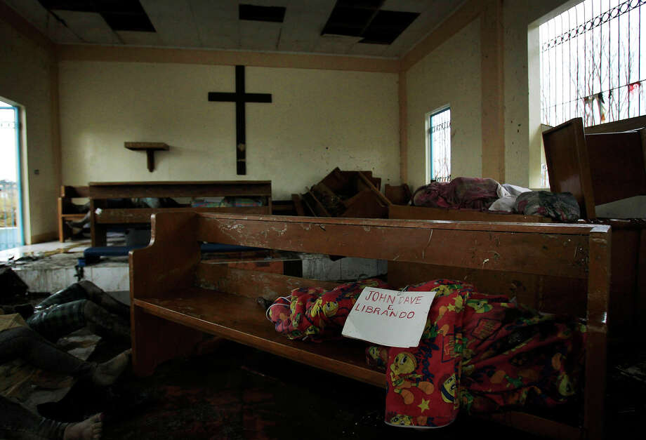 A body wrapped in cloth labeled only with a name is left on a pew at St. Michael The Archangel Chapel in Tacloban, central Philippines, Tuesday, Nov. 12, 2013.  There is no functioning morgue here, so people have been collecting the dead from Typhoon Haiyan and storing them where they can ó in this case, St. Michael The Archangel Chapel. Photo: Wally Santana, ASSOCIATED PRESS / AP2013